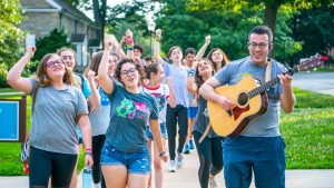 Campers singing and playing the guitar while walking