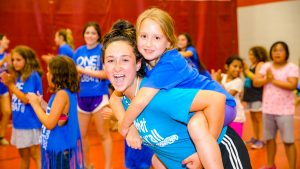 Counselor giving a camper a piggy back ride