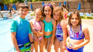 Campers in swimming gear by the pool