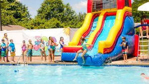 Campers sliding down the water slide into the pool